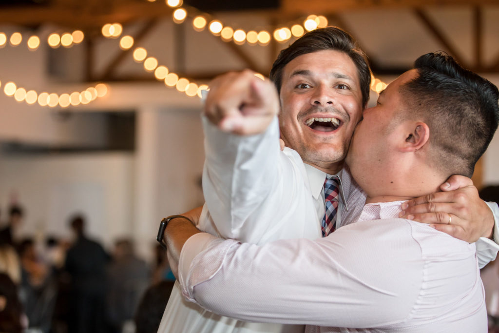 Happy friends hugging and celebrating at The Colony House wedding.