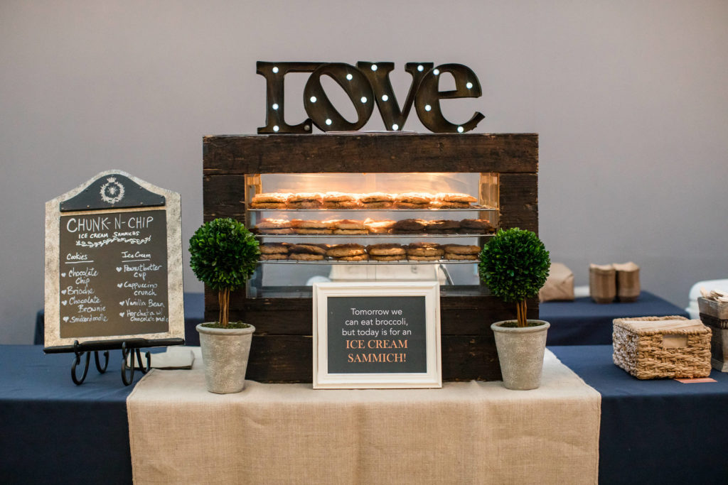 Ice cream sandwich bar set-up for wedding desserts with rustic wooden decor and navy details.
