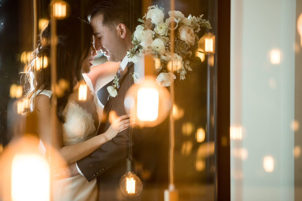 Bride and groom taking pre-wedding photos surrounded by hanging lights at The Colony House.