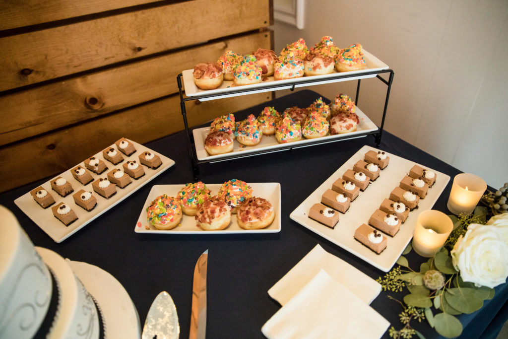Dessert bar set-up including sprinkled donut holes and cake slices for modern navy and grey wedding at The Colony House.