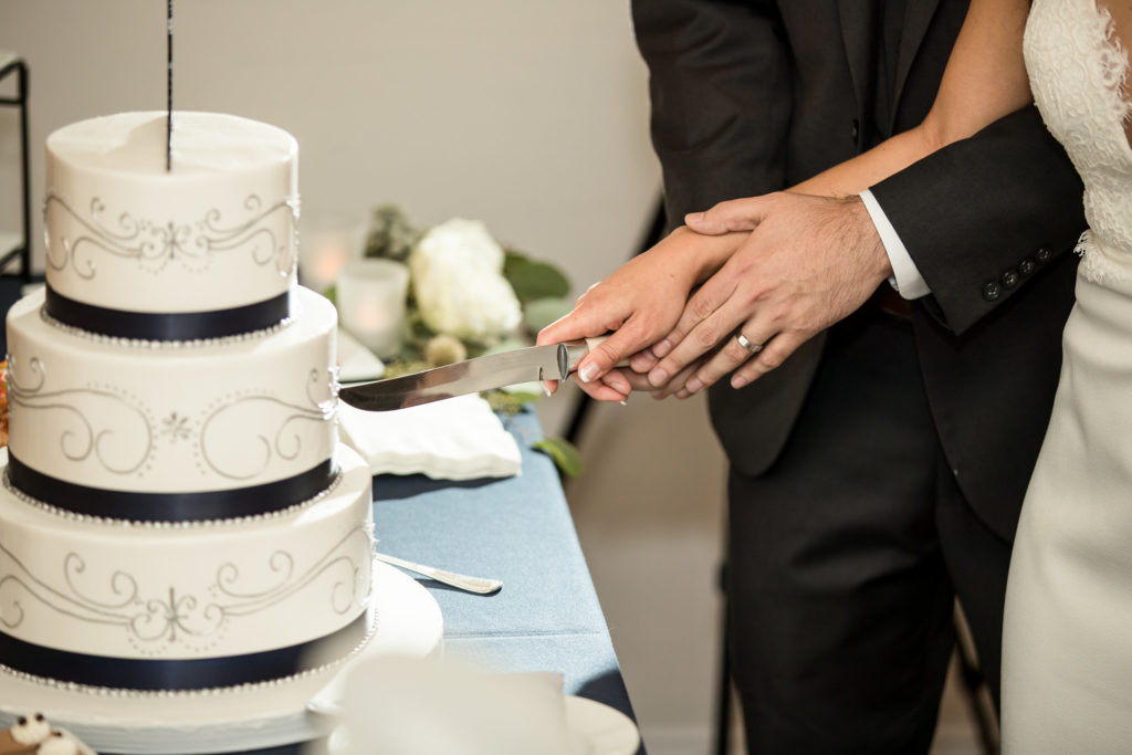 Bride and groom cut beautiful white 3-tier wedding cake with navy and silver details.