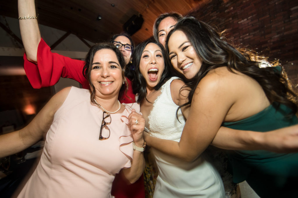 Bride and friends celebrating and dancing during reception at modern wedding at The Colony House.