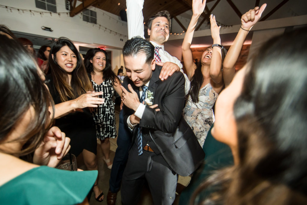 Groom and friends celebrating and dancing during reception at modern wedding at The Colony House.