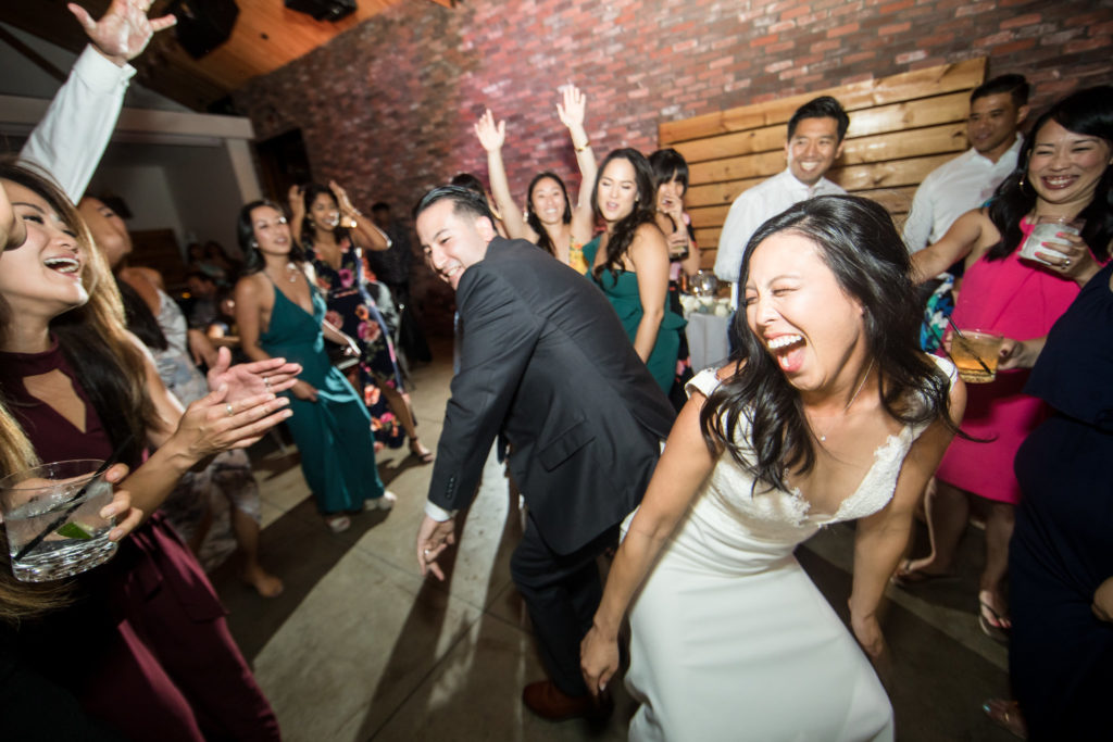 Bride and groom celebrating and dancing together during reception for modern wedding at The Colony House.