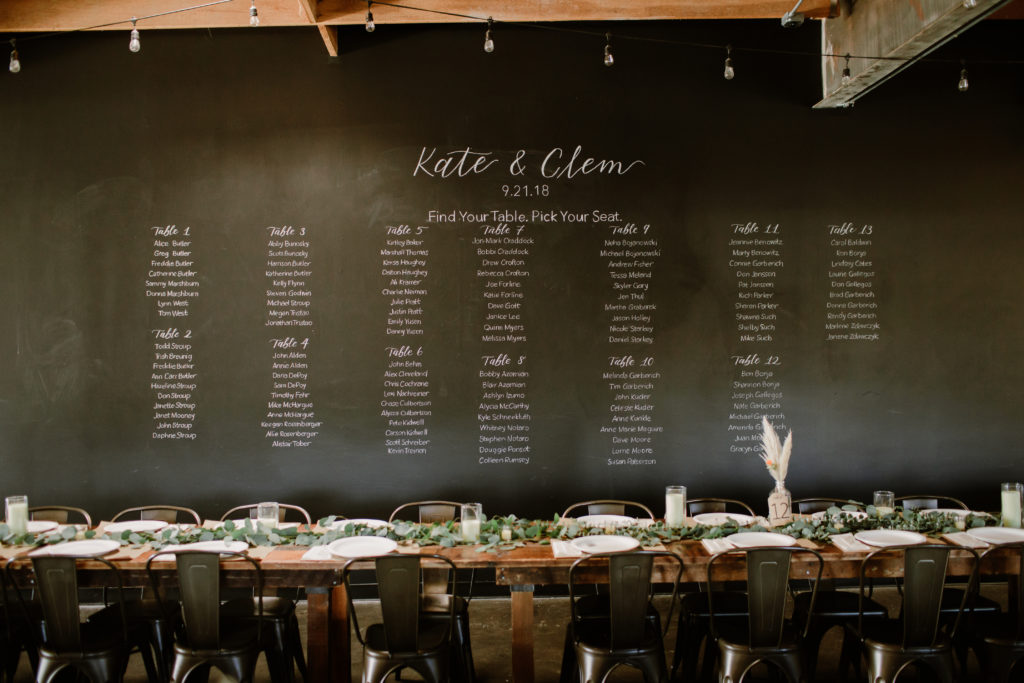 Seating arrangements on blackboard for rustic bohemian theme wedding at Smoky Hollow Studios
