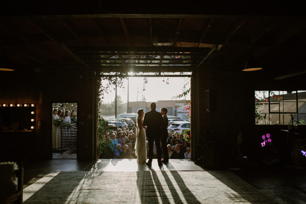 Couple saying vows under sunlight at Smoky Hollow Studios