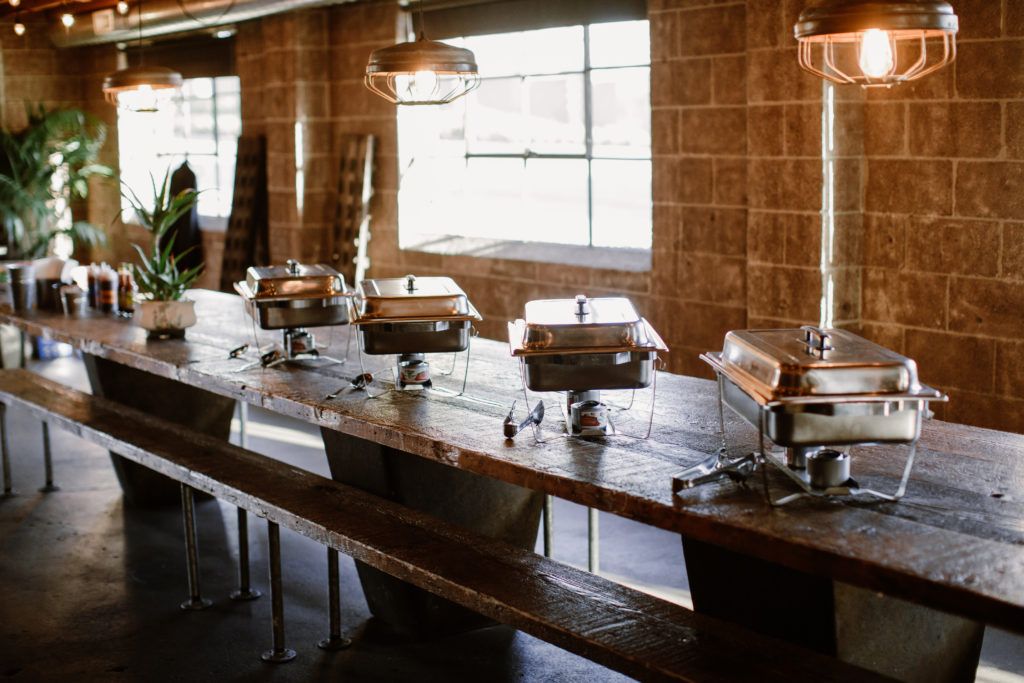 Buffet setup on long wooden farm tables for wedding reception