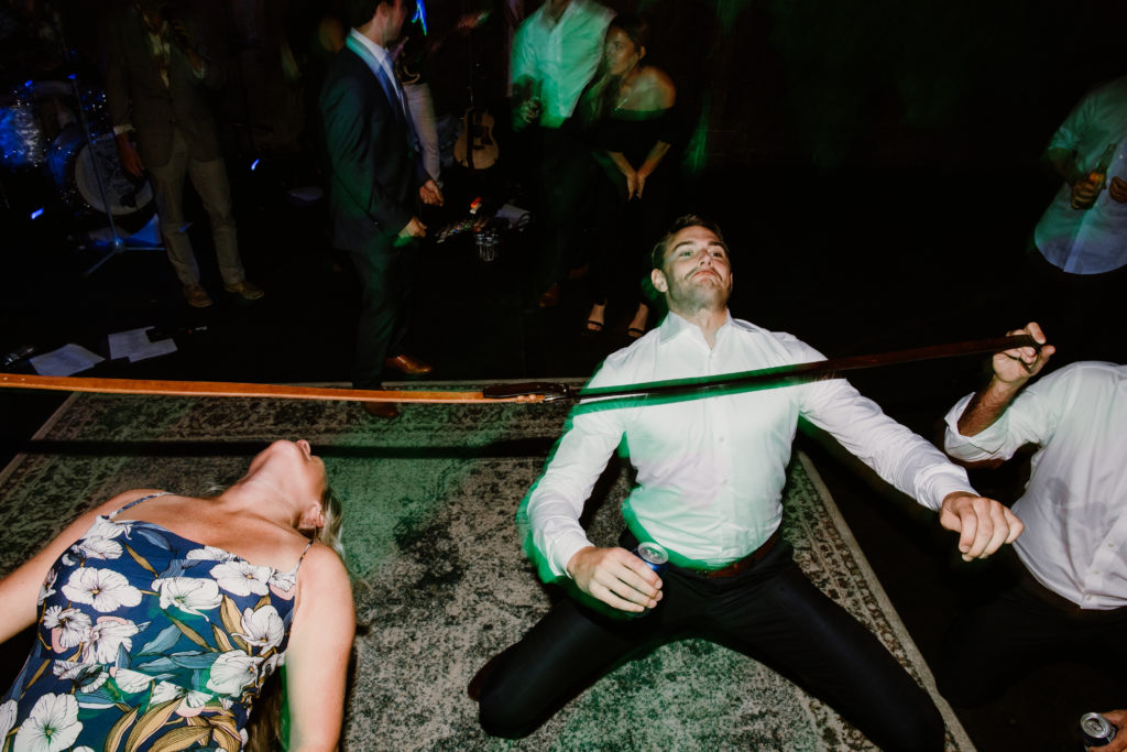 Friends doing limbo at wedding celebration