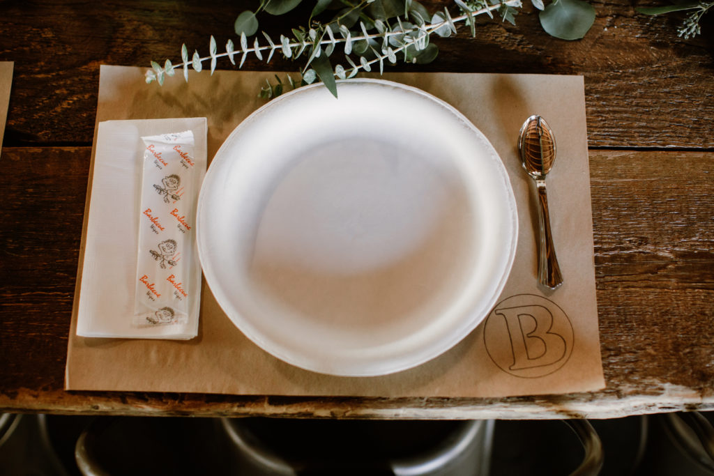 Place setting for BBQ at wedding on rustic wooden table