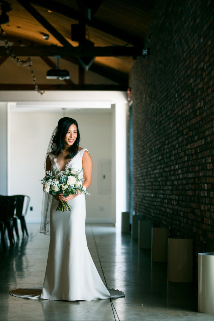 Beautiful modern bride with white floral bouquet posing before wedding at The Colony House in Anaheim.