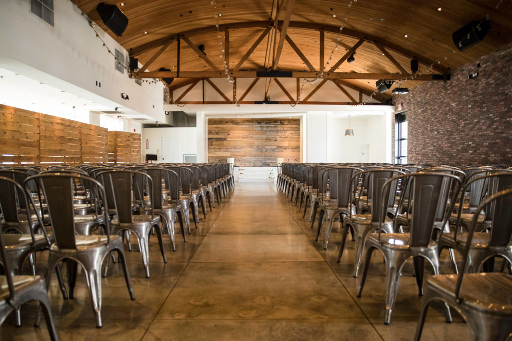 Indoor ceremony set-up with grey metal chairs and hanging lights for modern wedding at The Colony House