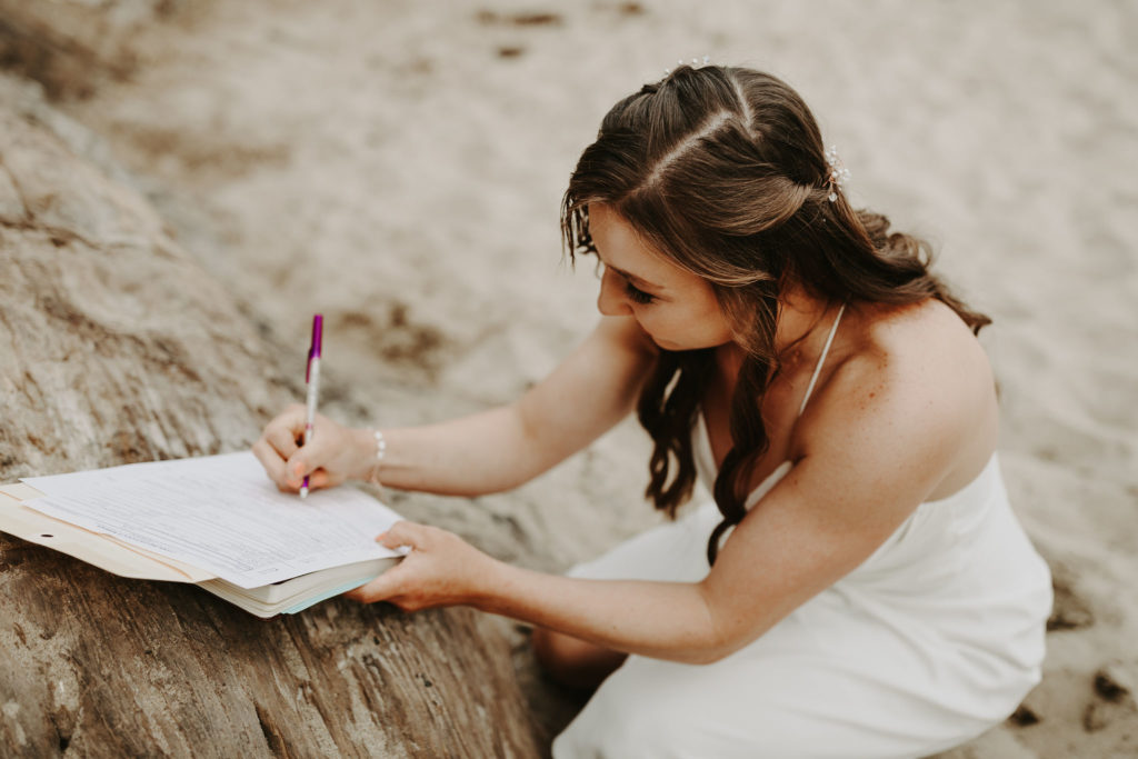Bride writing her vows in on the beach. How to write your wedding vows