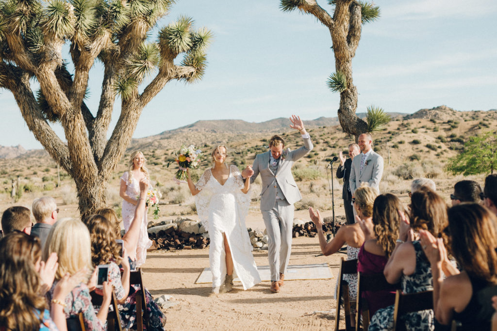 Bride in Grace Loves Lace dress with cape and groom in light grey suit at Rimrock Ranch in Joshua Tree