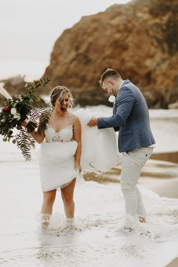 Bride laughing as wave gets bride and groom wet during elopement in Laguna Beach