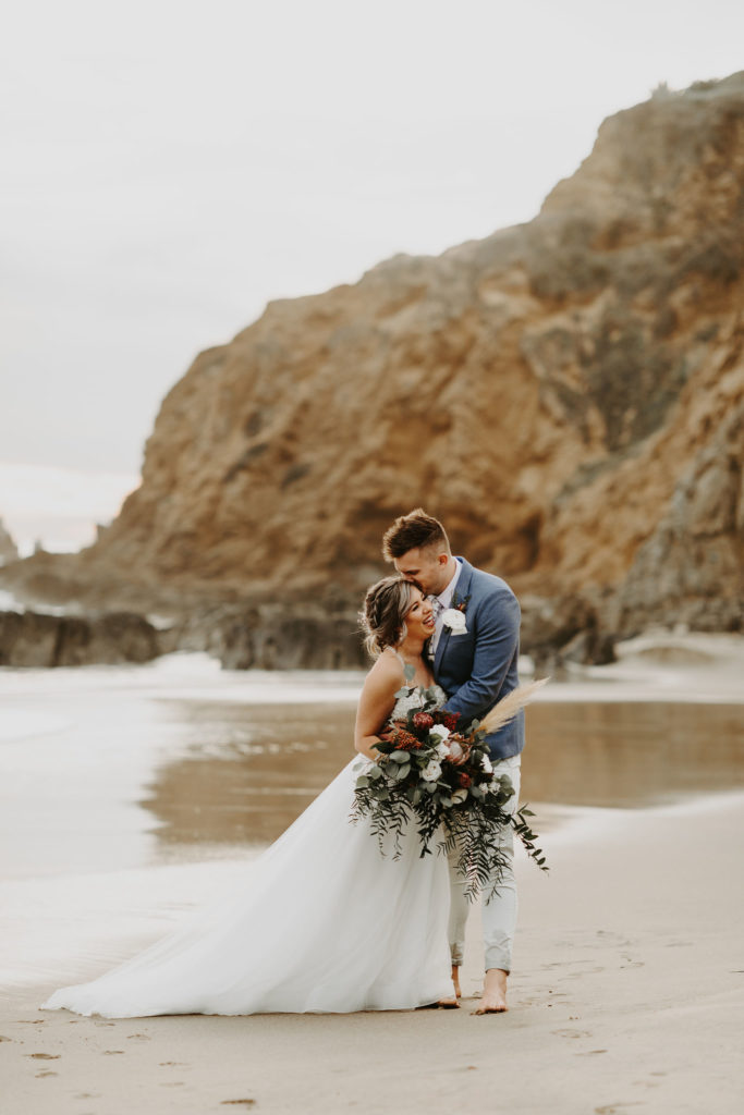 Bride and groom by the rocks in Laguna Beach after their intimate destination elopement