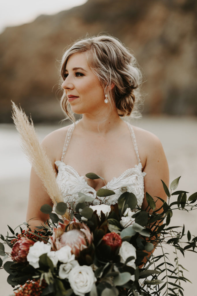 Bride with loose updo holding moody, wild bouquet in Laguna Beach