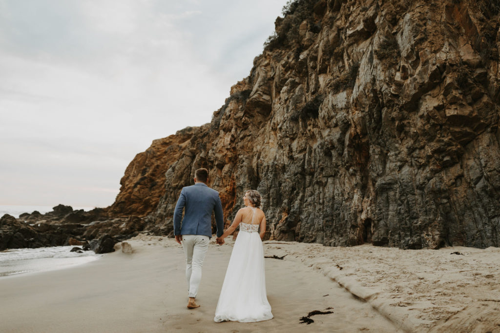 Bride and groom walk along the beach in Laguna Beach, CA after small elopement ceremony