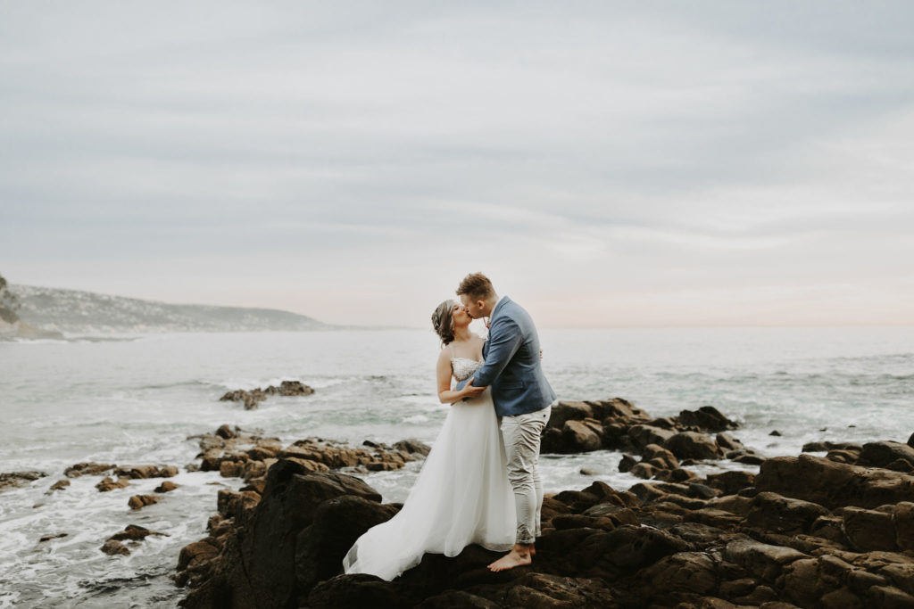 Bride and groom kiss on rocky cliff as waves crash behind them in Laguna Beach