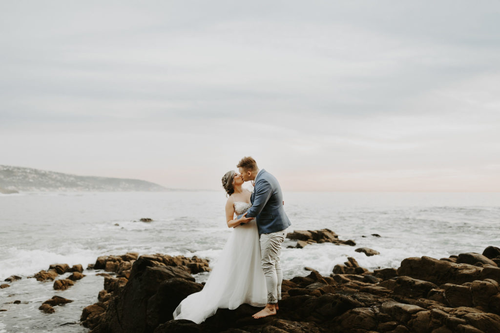 Bride and groom kiss on rocky cliff in Laguna Beach Elopement