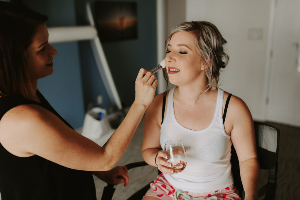 Bride getting ready with blonde updo and glass of rose for a Laguna Beach Elopement