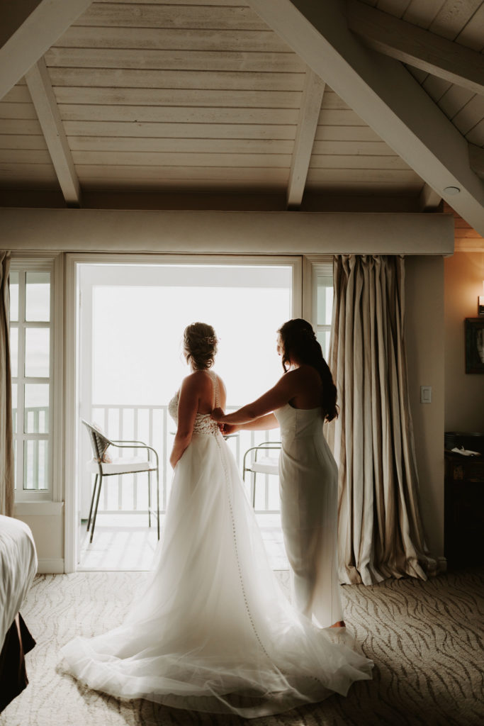 Maid of Honor helping bride get into dress for Laguna Beach elopement with ocean view