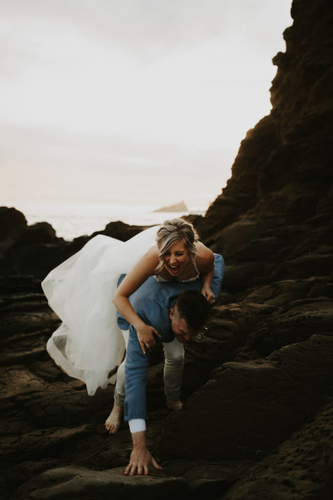 Bride and groom climbing rocks and laughing after elopement in Laguna Beach