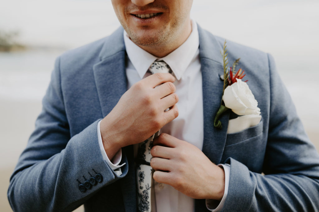 Groom in light blue suit and blue and white floral tie ready for elopement in Laguna Beach