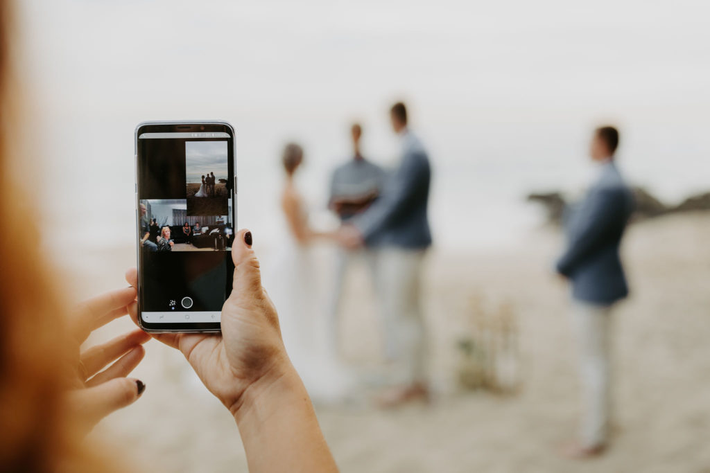 Skyping in the bride and groom's family on a phone during a surprise elopement on the beach in Laguna Beach California