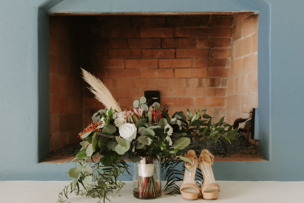 Wild boho bouquet with king protea and pampass grass and nude wedding shoes