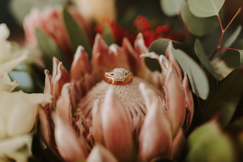 Rose gold engagement ring and band sitting on king protea flower