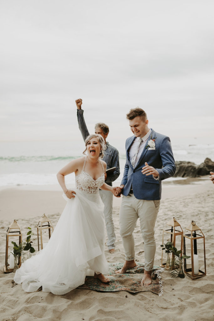 Bride and groom celebrate after getting married on the beach in Laguna Beach California