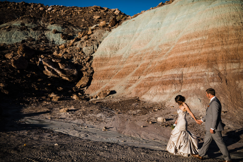 Bride and groom walking in the desert in Moab. Bride wearing a satin champagne dress and groom in light grey suit