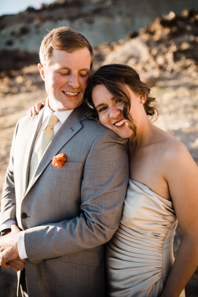 Bride and groom in the middle of the desert at Under Canvas Moab. Bride wearing champagne colored satin wedding gown