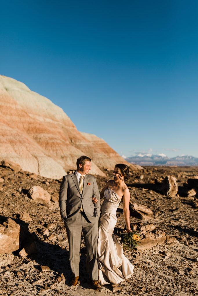 Bride and groom in the middle of the desert at Under Canvas Moab. Bride wearing champagne colored satin wedding gown.