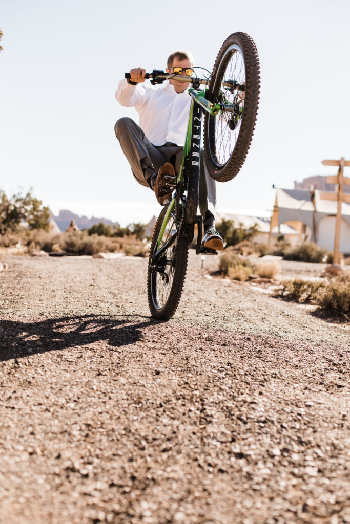 Groom riding mountain bike in the desert before wedding day. Wedding at Moab Under Canvas