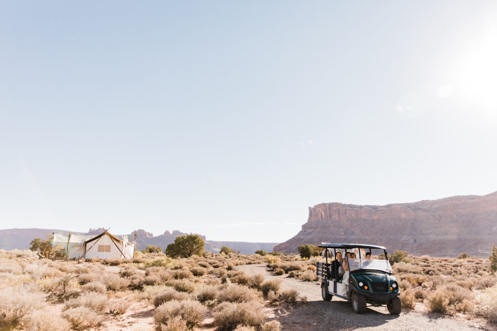 Bride and groom ride in golf cart after ceremony in the desert at Under Canvas Moab