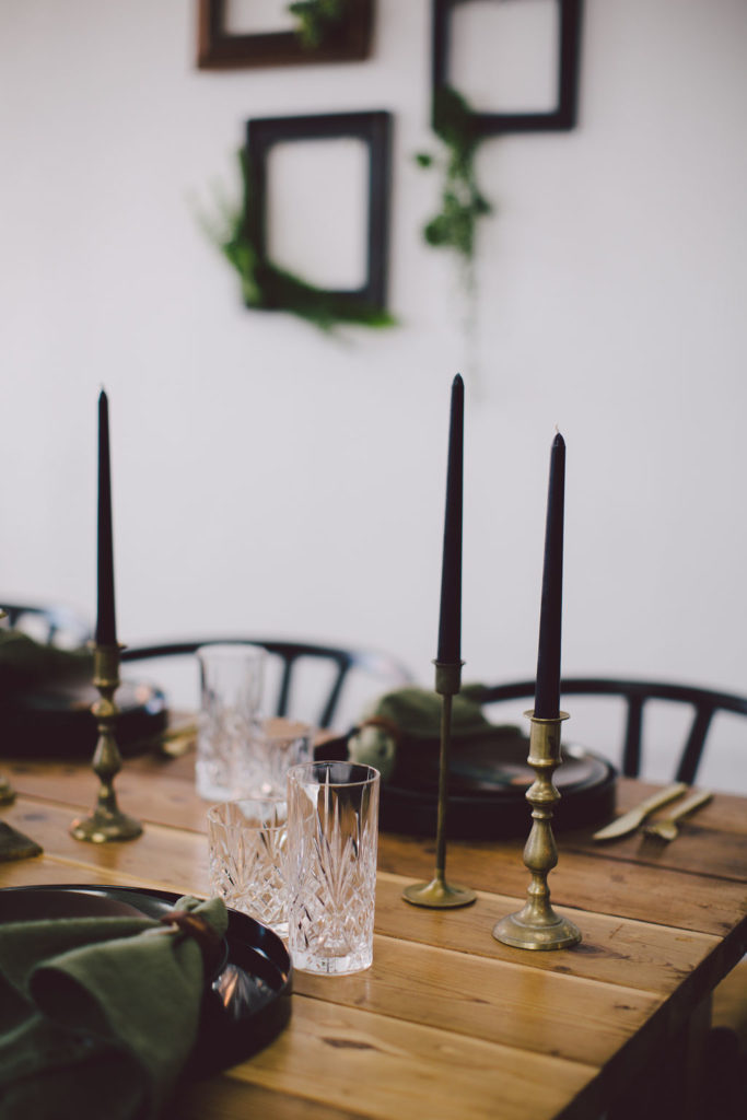 Black and gold candlesticks on wooden table with crystal glasses for elegant St Paddy's Day dinner party