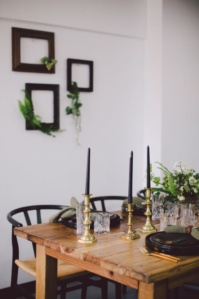 St Patrick's Day dinner party with tall black candles and dark green napkins. Black matte chargers, olive green plates and brown top plates for a masculine yet classy St Paddy's Day Dinner Party.