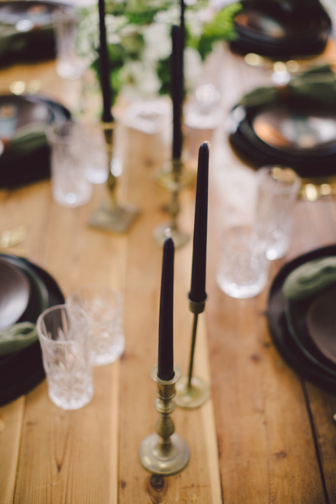 St Patrick's Day dinner party with tall black candles and dark green napkins. Black matte chargers, olive green plates and brown top plates for a masculine yet classy St Paddy's Day Dinner Party. Gold candlesticks with black candles on wooden table with greenery.