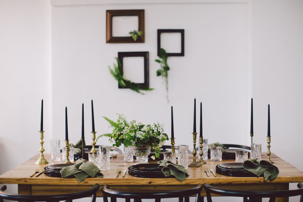 St Patrick's Day dinner party with tall black candles and dark green napkins. Frames with greenery coming out adds a fun nature element to the design