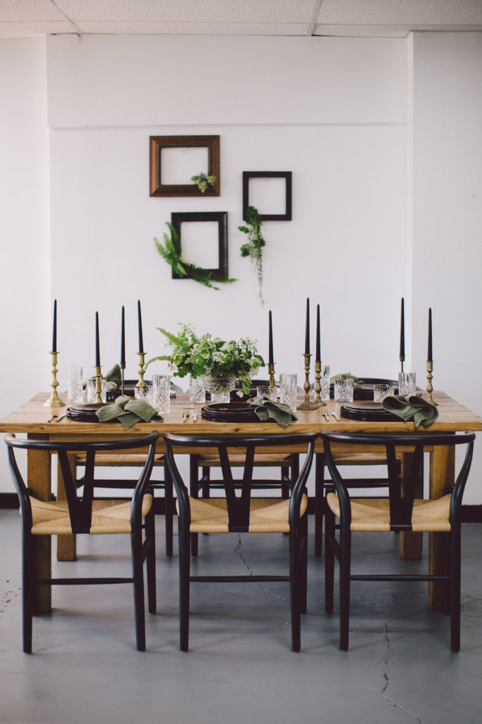 St Patrick's Day dinner party with tall black candles and dark green napkins. Frames with greenery coming out adds a fun nature element to the design. Black chairs and wood table with black matte plates and green, white and yellow florals.