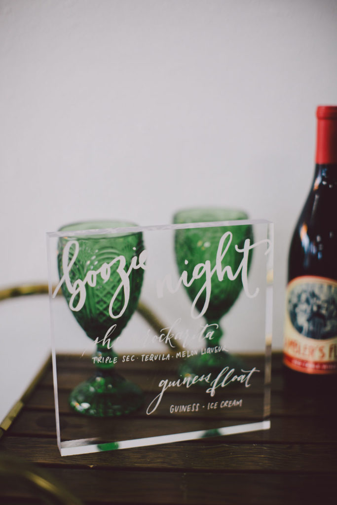 Green goblets with plexiglass bar sign on cute wooden bar cart for St Paddy's Day party