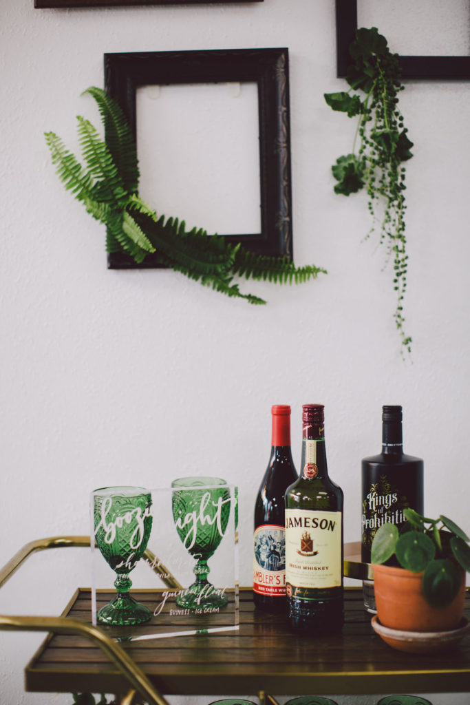 Wooden and gold bar cart with lot's of greenery for a St Patrick's Day Party. Green glassware, hanging plants from frames and a lucky horse shoe