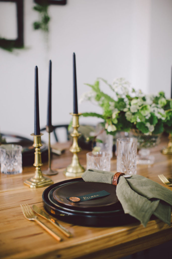 Olive green napkins with wooden napkin ring. Black plates and gold candles sticks with black candles are perfect for an adult St Patricks Day Dinner Party