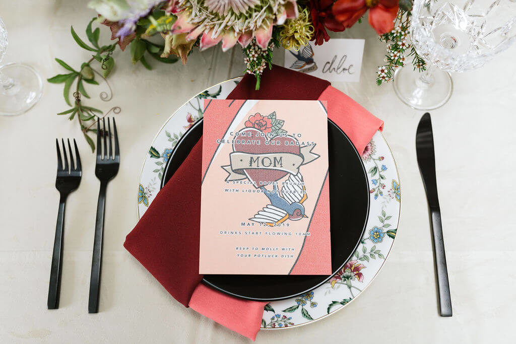 Colorful Mother's Day Brunch table with white velvet linen and black chairs. Pink and red napkins and invitations inspired by mom tattoos. Floral pattern plates are set with black matte flatware.