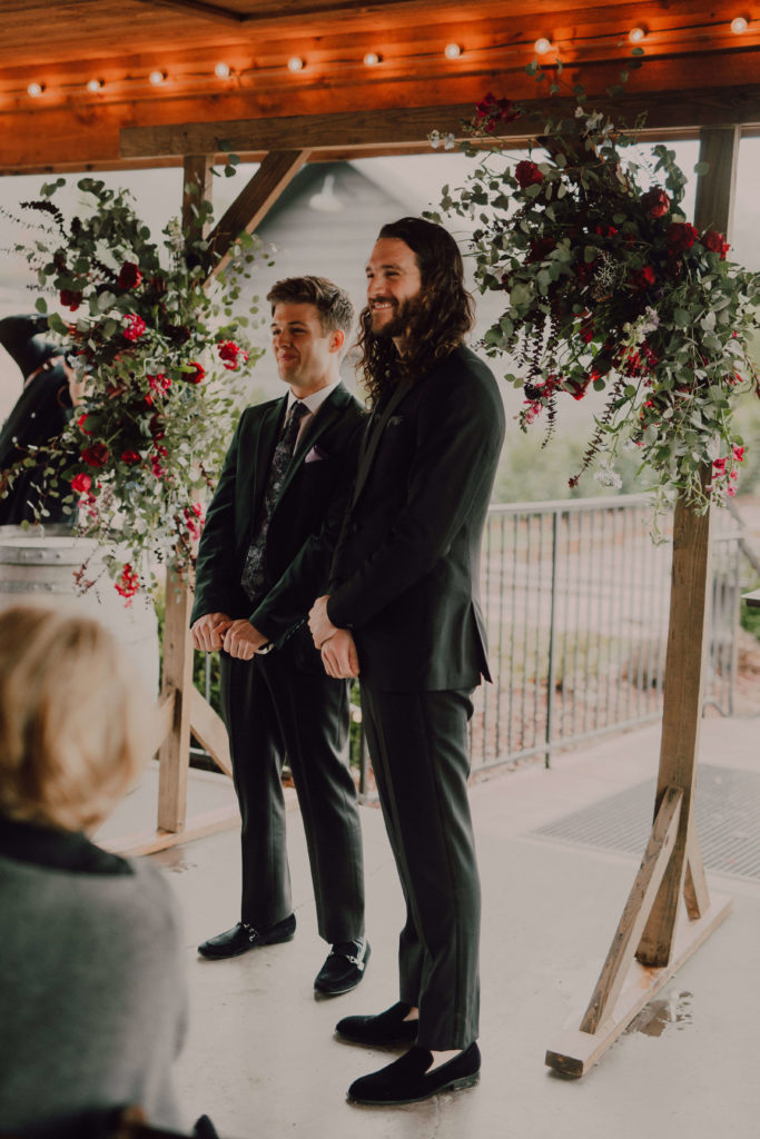 Groom waits at the alter at Arrington Vineyards with a beautiful wooden arch with lot's of greenery and pops of red and pink flowers  | Nashville Wedding Cause We Can Events