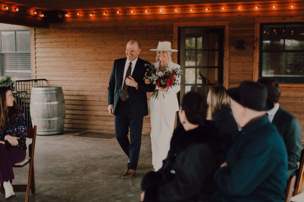 Bride in white pant suit and white boho hat walks down the aisle at Arrington Vineyards | Cause We Can Events | Nashville Wedding