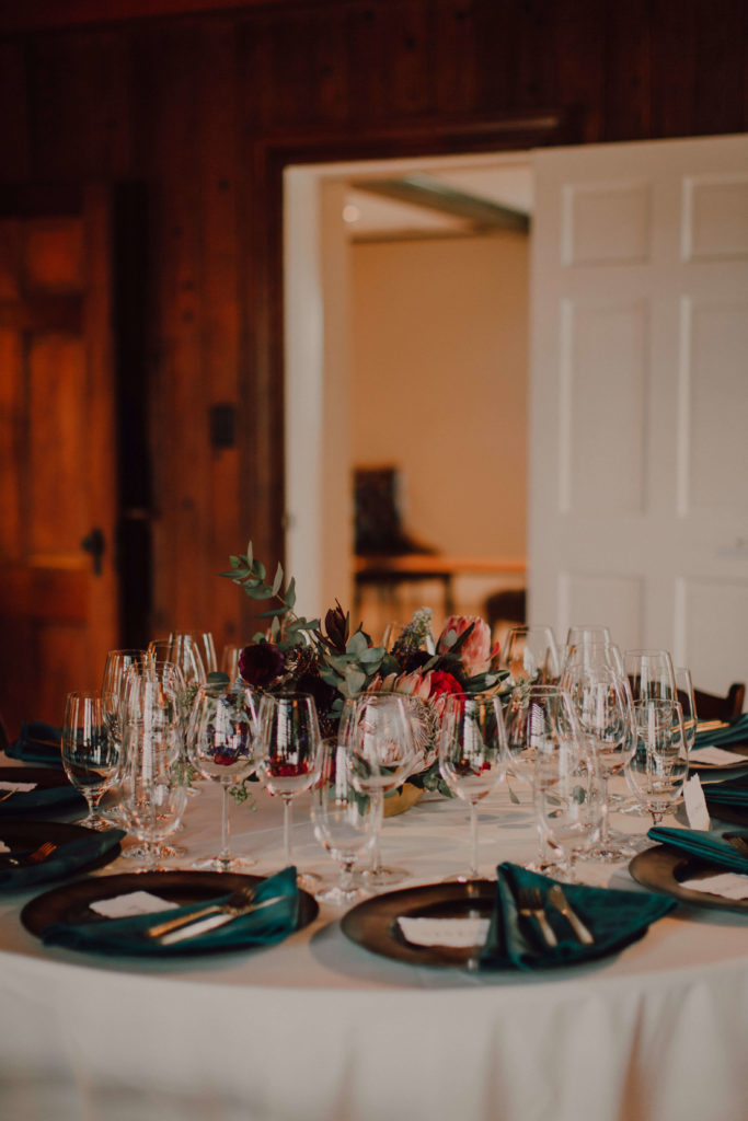 Winter wedding at Arrington Vineyards in Tennessee | Emerald velvet napkins with king protea centerpiece | Cause We Can Events | Destination elopement and weddings for adventurous couples
