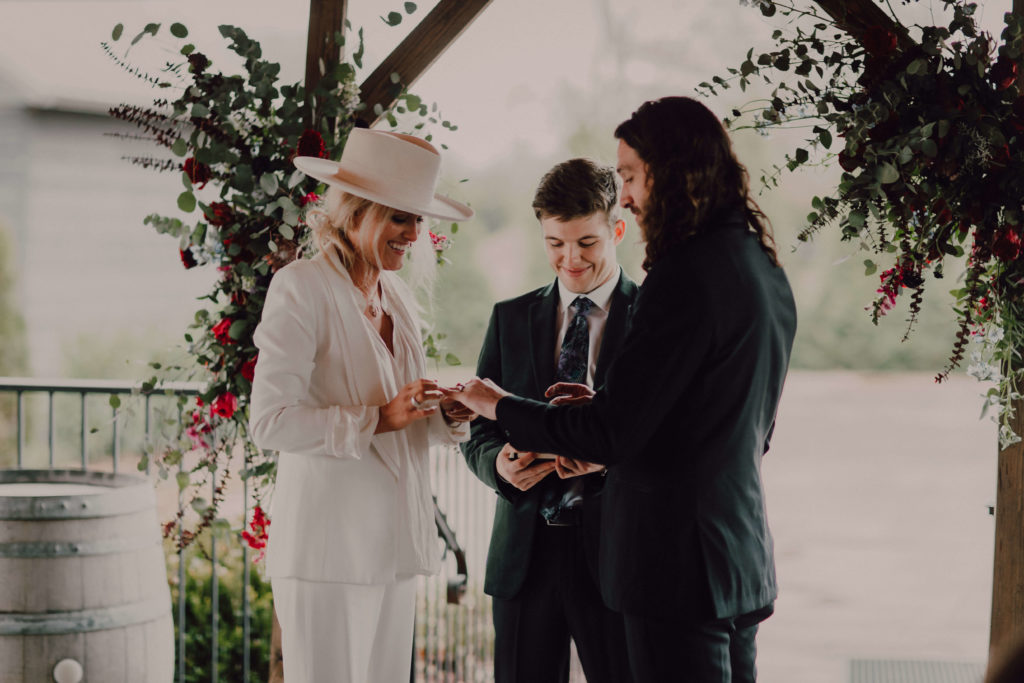 Intimate ceremony in Nashville, TN. Boho bride wearing trendy hat and white blazer