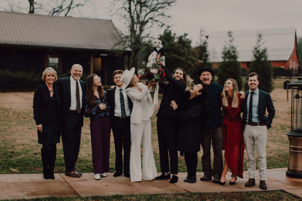 Wedding party and family laugh as groom lifts the dog of honor in the air to celebrate